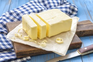 Fresh butter with knife on a chopping board