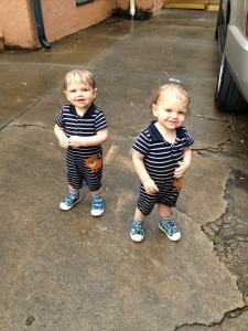 Twins playing in the rain