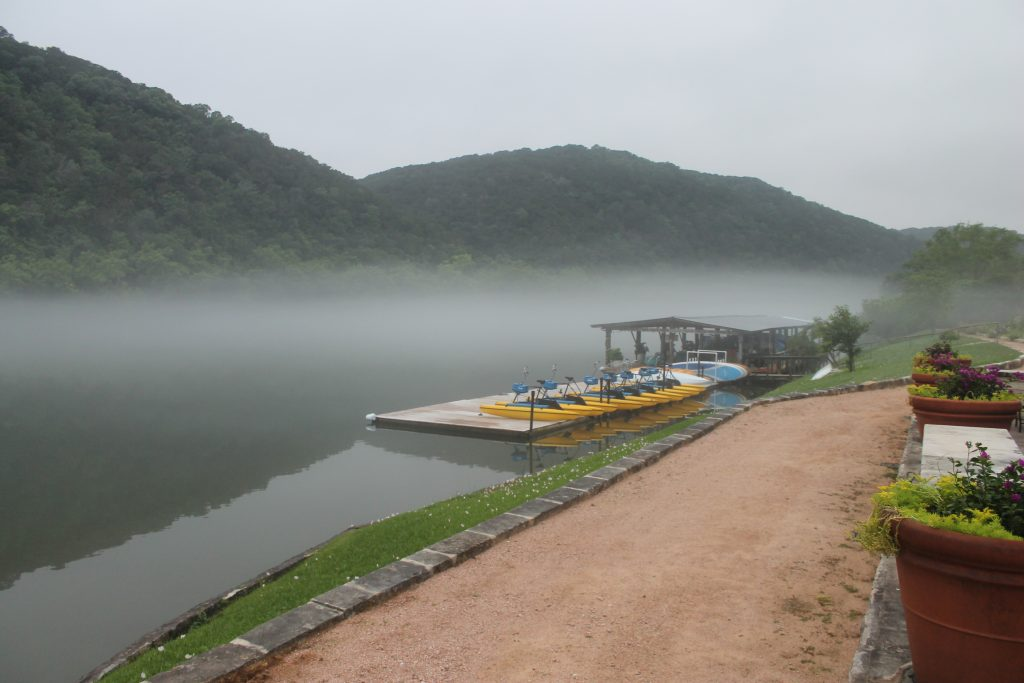 A misty Lake Austin and rolling hills